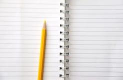Пожелтейте покрашенный карандаш на белой книге пробела картины нашивки Стоковое Изображение