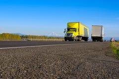 Пожелтейте semi трейлер тележки желтый на дороге с асфальтовыми породами стоковая фотография