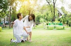 Пожилая азиатская женщина падая пока идущ для того чтобы сделать физическое с ручкой на парке, смотрителе принимает заботу и подд стоковые изображения rf