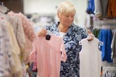 Пожилая бабушка женщины выбирая младенца одевает в магазине Стоковое фото RF
