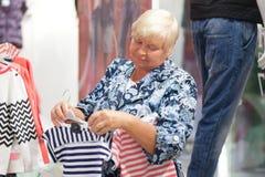 Пожилая бабушка женщины выбирая младенца одевает в магазине Стоковое Фото