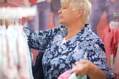 Пожилая бабушка женщины выбирая младенца одевает в магазине Стоковые Изображения RF