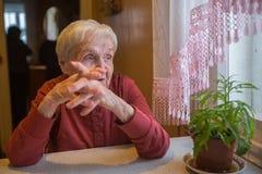 Пожилая дама сидит задумчиво около окна Портрет стоковые фотографии rf