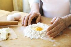 Пожилая женщина варит французские круассаны, оголяет сморщенные руки, ингридиенты, мягкий теплый свет утра, взгляд сверху Стоковая Фотография RF