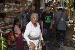 Пожилая женщина в фронте и другие люди в традиционной балийской одежде на церемонии кремации, остров Бали, Индонезия стоковое фото rf