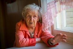Пожилая женщина говорит сидеть на таблице в доме Стоковое Изображение
