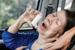 Пожилая женщина держа брызг астмы внутри автомобиля Стоковые Фотографии RF