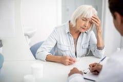 Пожилая женщина закрывая ее глаза и страдая от головной боли стоковые фотографии rf