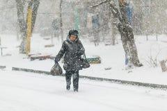 Пожилая женщина идет в снег на тротуаре, полагаясь на тросточке стоковая фотография rf