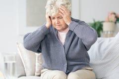 Пожилая женщина имея головную боль мигрени стоковое фото