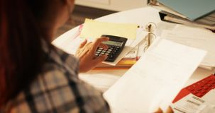 Пожилая женщина используя калькулятор для налогов и бюджета дома стоковые изображения rf