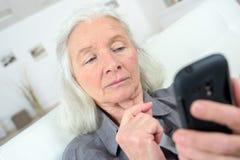 Пожилая женщина используя мобильный телефон стоковые фотографии rf