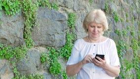 Пожилая женщина используя smartphone с наушниками Винтажная стена одичалого камня на заднем плане акции видеоматериалы