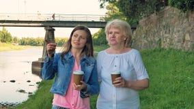 Пожилая женщина и милая маленькая девочка идут вдоль портового района и выпивая кофе Мост и стена года сбора винограда одичалого  видеоматериал