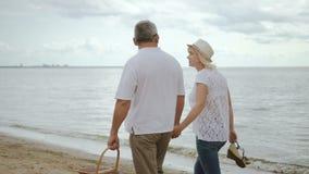 Пожилая женщина и мужской пенсионер двигая вдоль взморья акции видеоматериалы