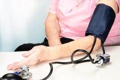 Пожилая женщина ожидает начала измерять кровяное давление с tonometer в оф стоковые фотографии rf
