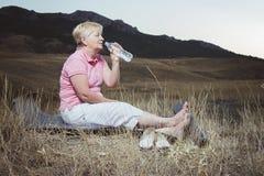 Пожилая женщина отдыхая после протягивать вечера Стоковое Изображение RF