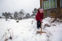 Пожилая женщина очищает снег около сельского дома активизма стоковое фото rf