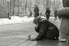 Пожилая женщина попрошайки на улице прося деньги нищенских Социальная проблема черная белизна стоковые фотографии rf