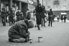 Пожилая женщина попрошайки на улице прося деньги нищенских Социальная проблема стоковое изображение