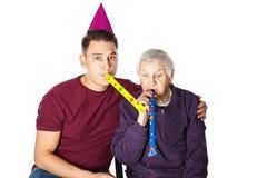 Пожилая женщина празднуя день рождения с внуком Стоковое Изображение