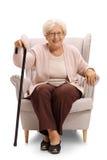Пожилая женщина при тросточка сидя в кресле стоковое изображение rf