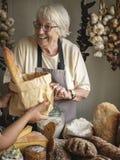 Пожилая женщина продавая хлеб на гастроном стоковые изображения rf