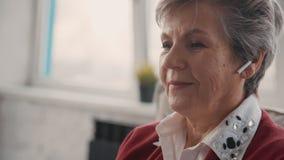 Пожилая женщина сидя в современном наушнике и усмехаться сток-видео