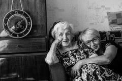 Пожилая женщина сидя на кресле с его взрослой дочерью Любовь Стоковые Фото