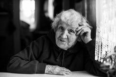 Пожилая женщина сидя на таблице Стоковая Фотография