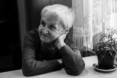 Пожилая женщина сидя на таблице Стоковое Фото