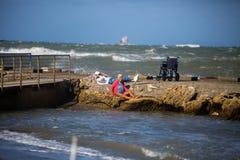 Пожилая женщина сидя на утесах и ее кресло-коляске около береговой линии на прогулке: Изменчивое море в ветреном дне стоковая фотография rf