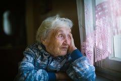 Пожилая женщина смотрит вне окно уныло стоковые изображения rf