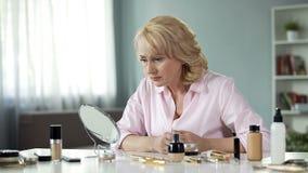 Пожилая женщина смотря грустно в зеркале с макияжем на таблице, процессом старения стоковое изображение