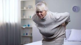 Пожилая женщина стоя вверх от кровати и внезапно чувствуя более низкой боли в спине, здоровья стоковые изображения rf