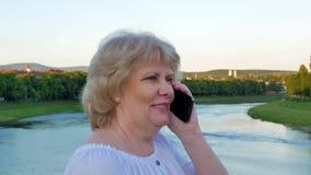 Пожилая женщина стоя на мосте над рекой и говоря на smartphone акции видеоматериалы