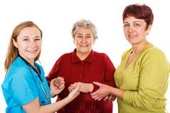 Пожилая женщина с человеком осуществляющим уход и молодым доктором стоковое изображение