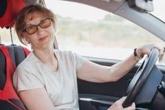 Пожилая женщина управляет автомобилем стоковое изображение