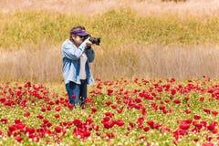 Пожилая женщина фотографируя поле с цветками Стоковые Изображения RF