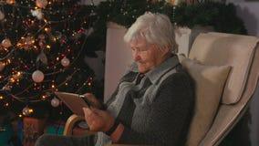 Пожилая женщина читает почты на таблетке акции видеоматериалы