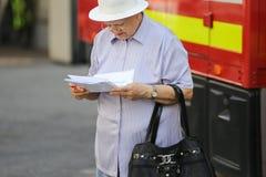 Пожилая женщина читая медицинский рецепт стоковые фото