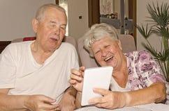 Пожилая пара наслаждается интернетом на таблетке стоковые фотографии rf