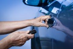 Пожилая рука женщины раскрывает автомобиль на ключевых аварийных системах Стоковая Фотография