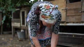 Пожилая сельская женщина держит кролика в ее руках Пугают и пробует сломать животное очень свободно Ферма кролика акции видеоматериалы