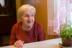 Пожилая счастливая женщина сидя на таблице Стоковая Фотография RF