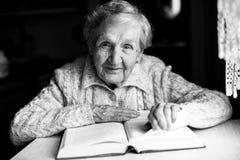 Пожилая счастливая женщина читая книгу Стоковое Фото