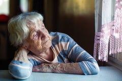 Пожилая унылая женщина сидит уныло около окна стоковые фотографии rf