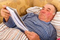 Пожилое чтение человека в кровати стоковое фото