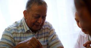 Пожилой гражданин взаимодействуя пока играющ шахмат 4k сток-видео