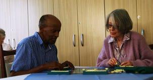Пожилой гражданин играя головоломку 4k видеоматериал